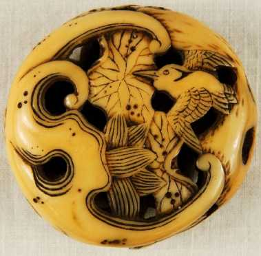 An Ivory Manju, carved and pierced in Ryusa style