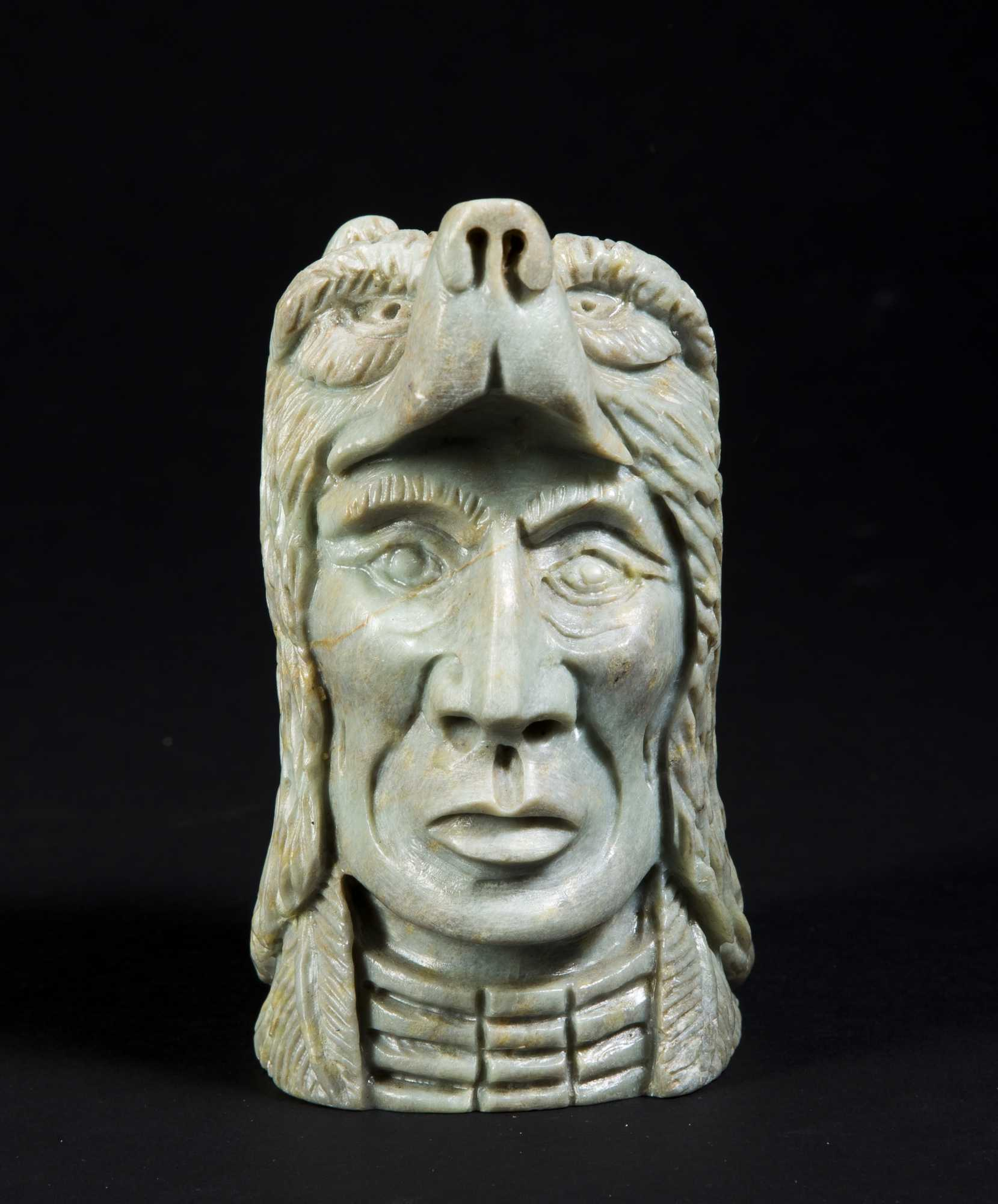 Two carved stone native american figures